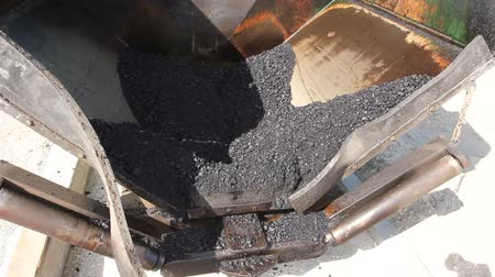 погрузчик : Front view on asphalt laying machine full of fresh asphalt at road construction site. Hot asphalt is spreading from paver machine on prepared ground.