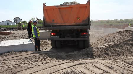 tracked : Zrenjanin, Vojvodina, Serbia - April 30, 2015:Dumper truck is unloading soil or sand at construction site.