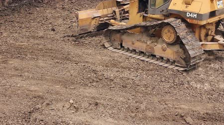 earthworks : Zrenjanin, Vojvodina, Serbia - May 21, 2015: View on bulldozer, crawler while he is moving and leveling ground at building site. Stock Footage
