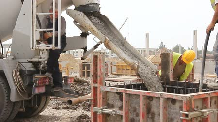 fitter : Zrenjanin, Vojvodina, Serbia - May 21, 2015: Workers at building site are pouring concrete in mold from mixer truck.