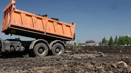 camionagem : Zrenjanin, Vojvodina, Serbia - May 30, 2015: Dumper trucks are unloading soil or sand at construction site.