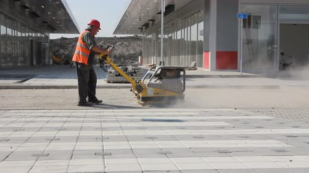 compacto : Zrenjanin, Vojvodina, Serbia - September 23, 2015: Worker is working with vibration plate compactor machine before pavement roadwork. Dust is flying around. Vídeos