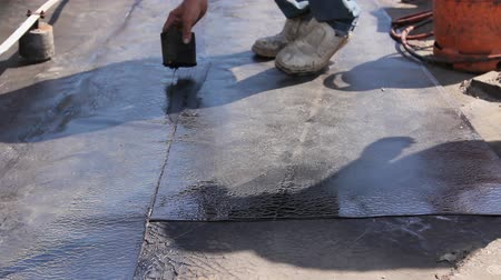 dekarz : Heating and melting of bitumen surface by flame from gas torch. Worker adjusts bituminous cover for roofing felt, smears melted resin with wooden tool.