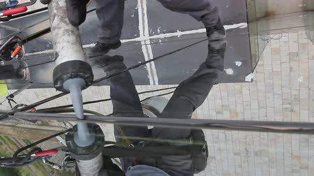 titular : Industrial climber is applying silicone to rubber juncture among building glass facade.