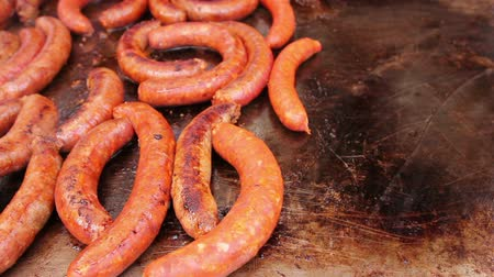 simmer : Hand with the help of metal tongs turns the sizzling sausages on metal plate, barbecue grill.