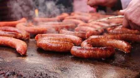 fogpiszkáló : Hand with wooden toothpick is making small holes in simmering sausages on a black barbecue grill.