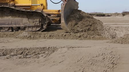 earthworks : View on bulldozer, crawler while he is moving and leveling ground at building site. Stock Footage