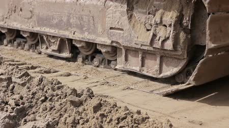 buldózer : Close up view on bulldozers undercarriage during pushing ground at construction site. Stock mozgókép