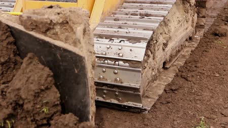 earthworks : Close up view on bulldozers undercarriage during pushing ground at construction site. Stock Footage