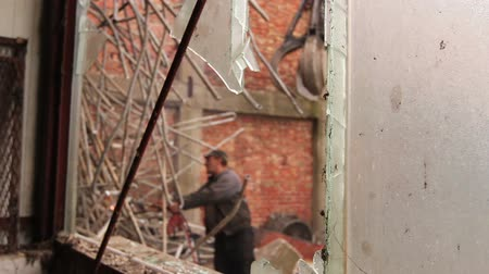 křaplavý : View trough broken window on worker who is cutting small tubes, obsolete industrial equipment with acetylene torch. Photo - JPEG video codec
