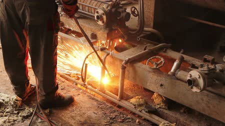 instalações : Worker is cutting manually old, scrap, metal construction using gas mixture of oxygen and acetylene, propane.Photo - JPEG video codec