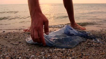 převrátit : Man is with hand fingers is touching carcass of dead huge blue jellyfish washed up by the sea on sandy beach. Photo - JPEG video codec Dostupné videozáznamy
