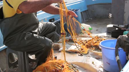pulling rope : Fisher in rubber trousers and boot is sitting in his boat and pile up fishing net for angling at open sea. Photo - JPEG video codec