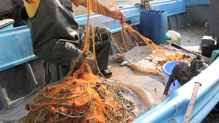piled up : Fisher in rubber trousers and boot is sitting in his boat and pile up fishing net for angling at open sea. Photo - JPEG video codec