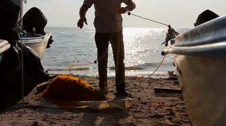 pull out : Fisher pile up fishing net at sandy beach. Fisherman is taking out fish from net and prepare for his next angling. Photo - JPEG video codec Stock Footage