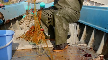 allontanare : Fisher in rubber trousers and boot is sitting in his boat and pile up fishing net for angling at open sea. Photo - JPEG video codec