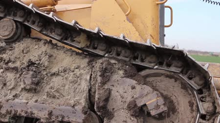 earthworks : Close up view on bulldozers undercarriage during pushing ground at construction site. H.264 video codec