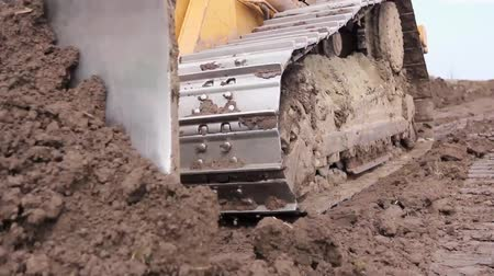 earthworks : View on bulldozer, crawler while he is moving and leveling ground at building site. H.264 video codec