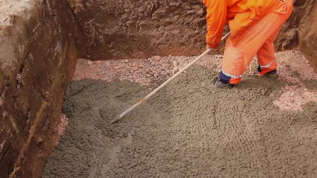 dengeleme : Worker is leveling concrete after pouring. Mason is using rake to spreading fresh concrete in square trench. H.264 video codec