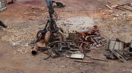 rozsdásodás : Above view on loader manipulator with hydraulic grappling claw until is collecting, moving old steel, scrap metal. H.264 video codec