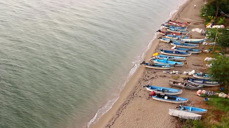 ужение : Small angling boats are dry docked on the beach. Above view on fishing boats that are dry docked, withdrawn at the sandy beach, coastline. H.264 video codec