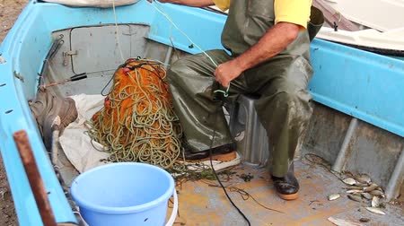 pulling rope : Fisherman is empty fish from net in his small boat. Fisher in rubber trousers and boot is sitting in his boat and pile up fishing net for angling at open sea. H.264 video codec Stock Footage