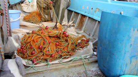çekme : Fisherman is empty fish from net in his small boat. Fisher in rubber trousers and boot is sitting in his boat and pile up fishing net for angling at open sea. H.264 video codec Stok Video