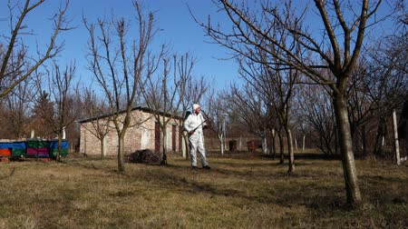 püskürtücü : Farmer in protective clothing sprays fruit trees in orchard using long sprayer to protect them with chemicals from fungal disease or vermin at early springtime.
