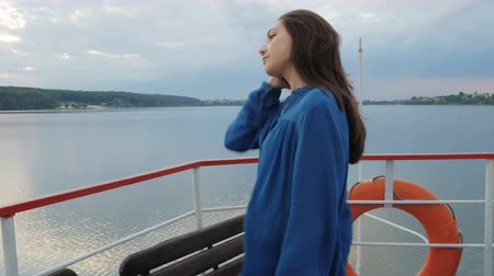 podróżnik : Travel, trip, vacation, tourist concept. Happy smiling young woman, female Asian mixed, traveling in a blue shirt, sailing on a passenger ship or boat in the summer on the lake sunset