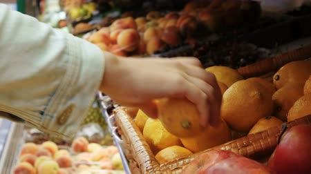 críquete : Woman hand choosing lemons at the grocery store picks up lemons at the fruit and vegetable aisle in a supermarket