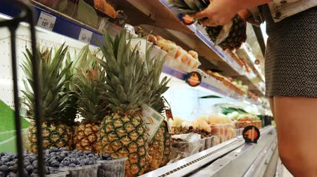 críquete : Woman Selecting choosing Pineapple a in supermarket.