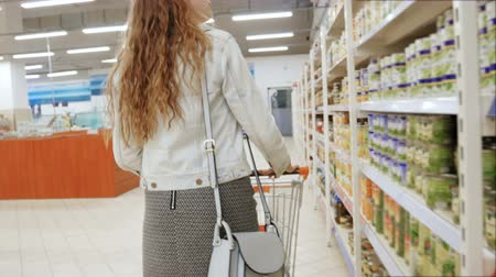 críquete : Young woman chooses canned food in the store. Shopping at the supermarket, follow shot from back Stock Footage