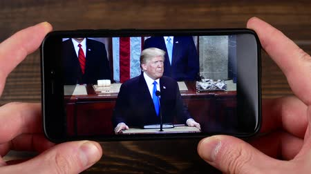 başkan : Ternopil, Ukraine - February 19, 2018: looks at the USA President Donald Trump on smartphone Stok Video