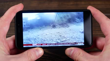 isis : Ternopil, Ukraine - February 19, 2018: watch the news about Syria on a smartphone