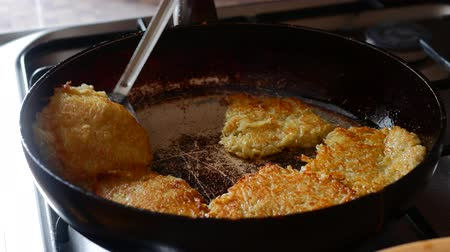 оладья : cook of golden crispy potato pancakes in a frying pan