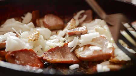 The cook pan fries meat. The man fries meat on the burning frying pan. Fire on a frying pan. Close up. Roasting of meat fire on a frying pan. Стоковые видеозаписи