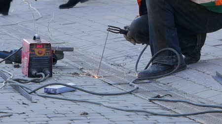 laboring : A man with face protection welds metal parts. The welder is working on the street.