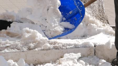 shoveling manually white snow from the street with shovel, clearing frozen path. Winter job and removal of deep snowy blanket, digging, scooping, throwing it on pile Стоковые видеозаписи