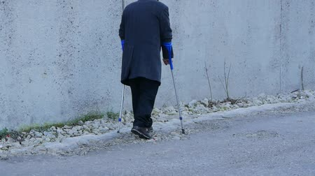 kule : elderly handicapped people background. old man walks in public with crutches.
