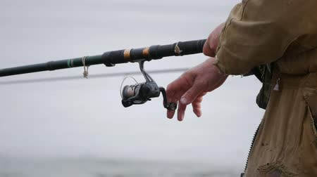 Close-up of a fishermans hand with a fishing rod
