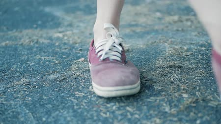 UKRAINE, TERNOPIL - May 25, 2018: the girl kicks dirt or trash on the road. focus on legs in red sneakers Wideo