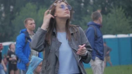 UKRAINE, TERNOPIL - July 20, 2018: girl hippie with phone in hands and sunglasses dancing at the festival Wideo