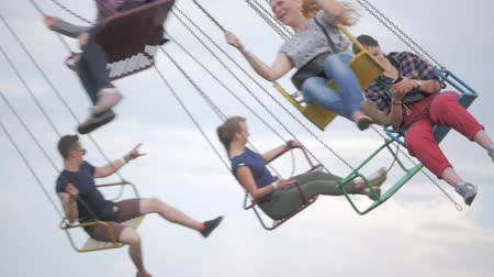 UKRAINE, TERNOPIL - July 20, 2018: Happy teenage best friends riding the chairoplane carousel and having fun at the funfair