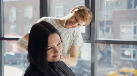şifoniyer : Male hairdresser smiling and talking with a customer while making a new haircut to beutiful young brunette woman Stok Video
