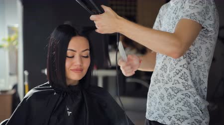 žehlení : Beautiful woman happy while hairdresser is straightening her hair in salon. New haircut or hairstyle for young woman. Dostupné videozáznamy