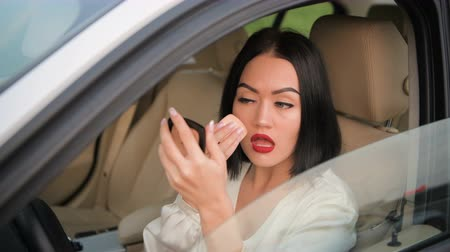 rouge : Beautiful elegant brunette woman with red lipstick on her lips applying makeup powder in her expensive car decorated with white leather interior