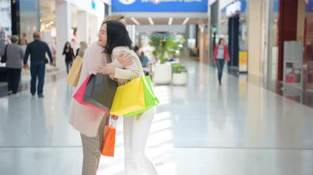 metáfora : Two happy young girls meet with a hug in a department store while shopping.