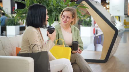 tea bag : Two young women drinking coffee, talking and laughing at cafe in the mall after shopping. People, friendship, conversation and togetherness concept Stock Footage