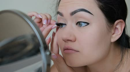 kiterjesztés : Woman attach false eyelashes to herself in slow motion HD