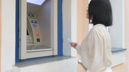 bankomat : Attractive young business woman is inserting a credit card to withdraw some money.